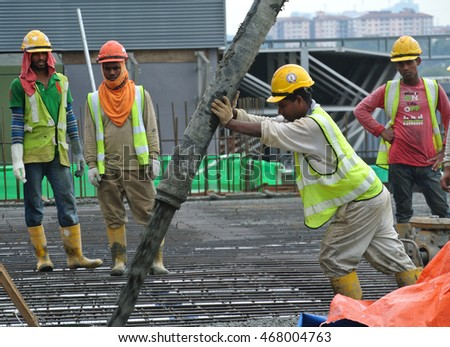 PERAK, MALAYSIA -JULY 26, 2016: SELANGOR, MALAYSIA â?? MAY 2014: Construction workers are doing the concreting work using hose from the elephant crane or concrete pump crane at the construction site.