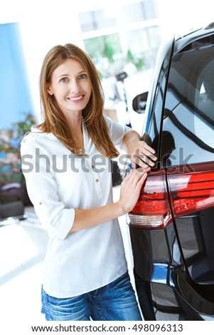 Perfect car for my roadtrips. Vertical portrait of a beautiful mature woman leaning on her newly bought car smiling to the camera joyfully