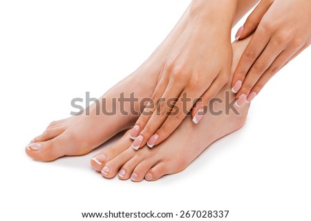 Perfect feet. Cropped picture of a beautiful young woman touching legs while sitting against white background