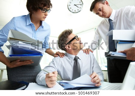 Perplexed accountant looking at his partner holding huge piles of documents
