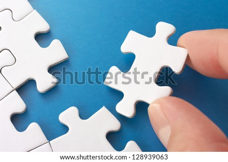 Person assembling puzzle pieces.Concept image of building and growth.