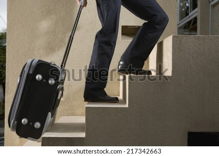 Person pulling luggage up stairs