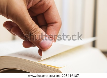 Person turning the page of a book up close