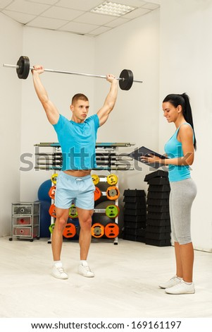 Personal female trainer watching young man who lifting barbells. Selective focus on man