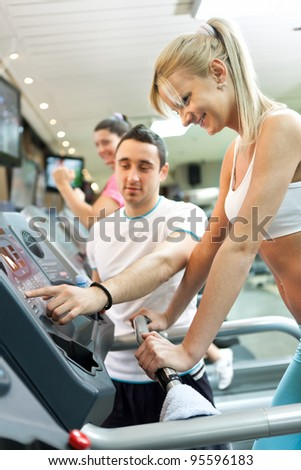 personal trainer instructing woman  how to use treadmill