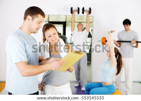 Personal trainer showing a woman exercise plan, a group behind them exercising.