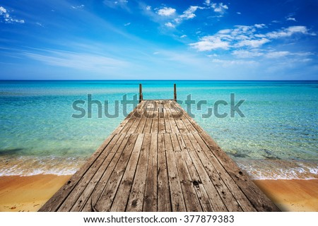 Perspective view of a wooden pier on the seashore with clear blue sea
