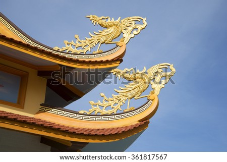 PHAN THIET, VIETNAM - DECEMBER 24, 2015: Fabulous birds on the curves of the roof of a Buddhist pagoda