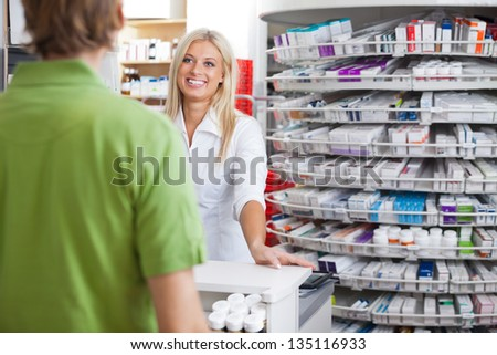 Pharmacist helping customer at counter