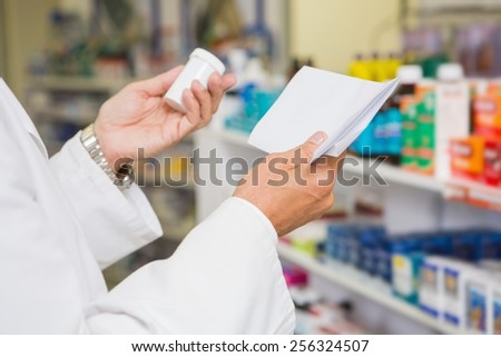 Pharmacist reading prescription and holding medicine in the pharmacy