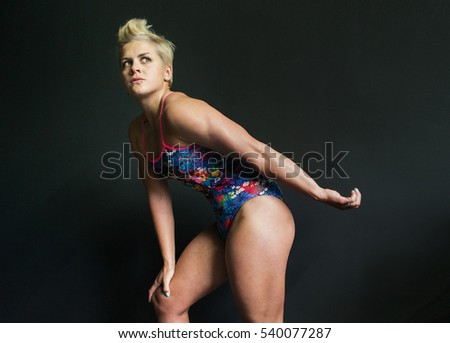 photo athletic girl posing in a swimsuit gray background
