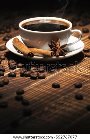 photo background of breakfast: hot coffee flavored with anise and cinnamon sticks on wooden texture