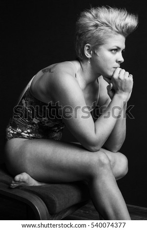 photo bodybuilder girl sitting on a stool in swimsuit black and white