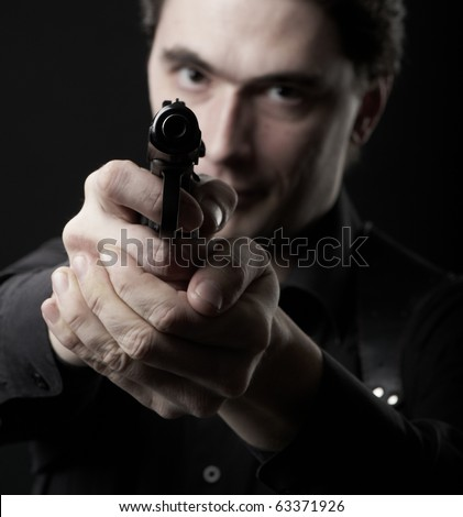 photo dark man pointing a gun looking at the camera