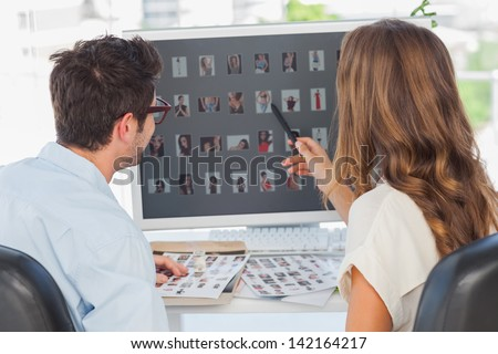 Photo editor pointing at computer while working on computer with a colleague