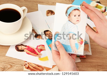 Photo in hands and cup of coffee on wooden table