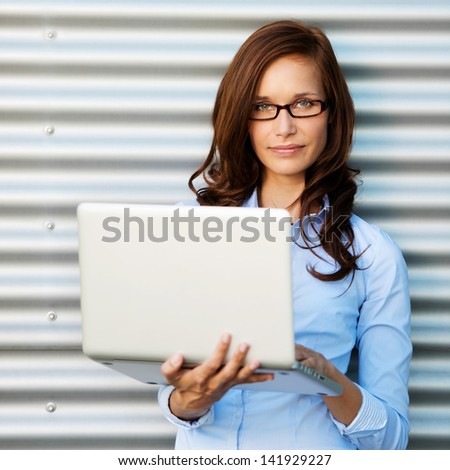 Photo of a beautiful woman posing for the camera while holding her laptop.