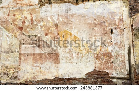 Photo of a colorful old decaying brick wall with peeling paint and stucco. Great for a background image or a texture.