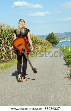 Photo of a female guitarist walking down a country road with her guitar slung over her back.