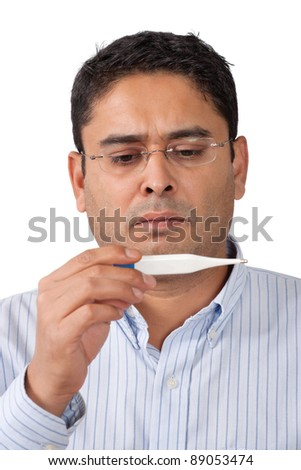 Photo of a middle-aged man looking at thermometer with worry.