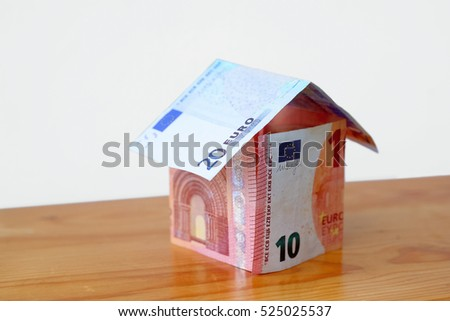 Photo of a model house made from Euro banknotes on the table