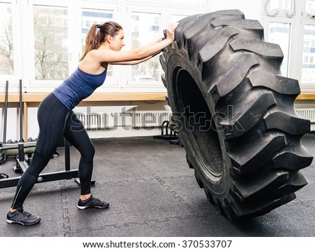 Photo of an attractive young woman working out with a tractor tire at a crossfit gym.