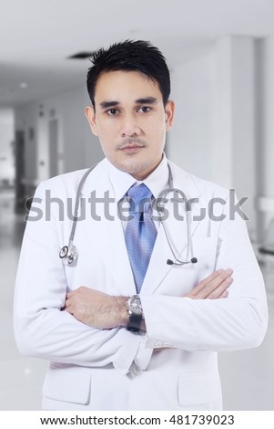 Photo of Asian male doctor wearing uniform and standing in the clinic corridor while looking at the camera