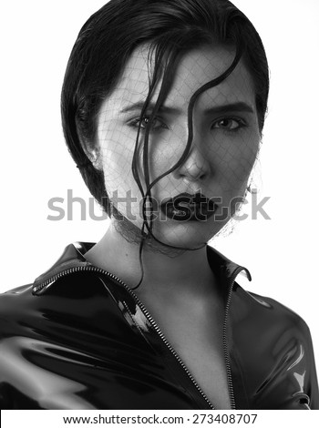 Photo of beautiful young woman in latex with magnificent hairstyle and grid. The Black-and-white photo