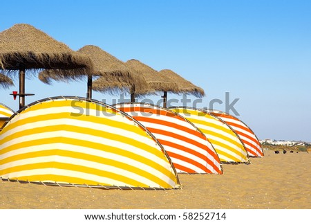Photo of colorful beach sun-shades and deck-chairs