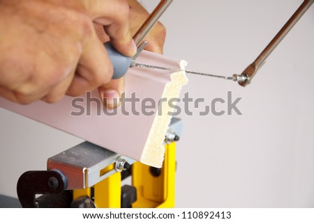 Photo of coping saw being used on piece of trim