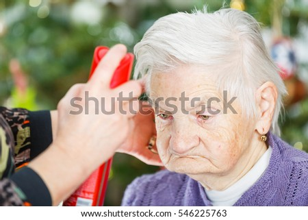 Photo of elderly woman helped by her caregiver