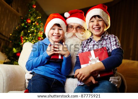 Photo of happy boys holding gifts with Santa Claus between them