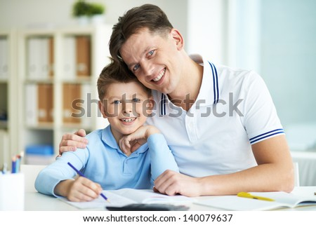 Photo of happy man and his son looking at camera