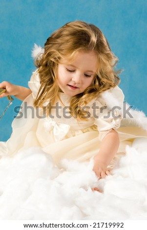 Photo of pretty girl in angelic costume on a blue background
