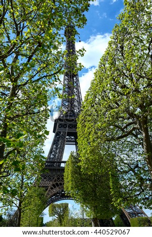 photo of the Eiffel Tower on a sunny day. with clouds. through foliage