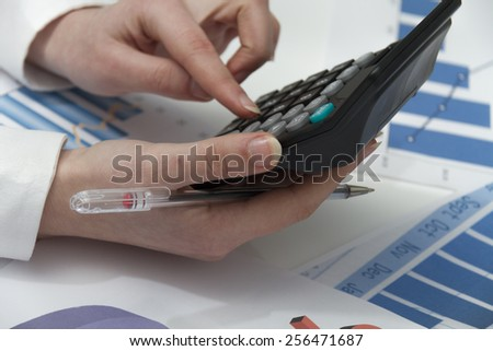 Photo of the Young businesswoman calculating financial documents