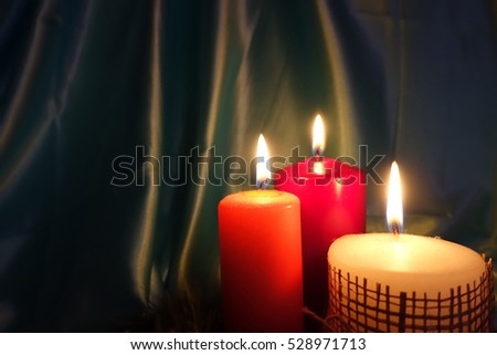 photo of three Christmas candles with flame