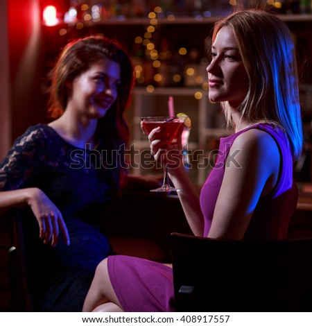 Photo of two young women sitting at bar