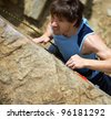 Photo of young man climbing up the rock - stock photo