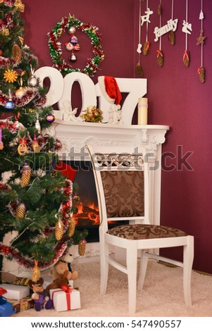 Photo Studio near Christmas tree with presents and fireplace. Christmas motif.