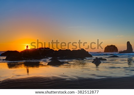 Photograper shooting sunset at Bandon Beach over the Pacific ocean with reflections on wet sand, Bandon, Oregon