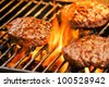 Photograph of three tasty beef burgers on the grill - stock photo