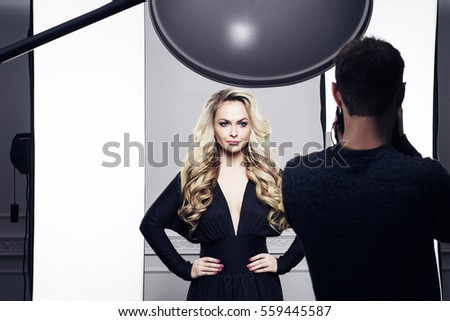 Photographer and beautiful model in working process. Fashion, photography concept.