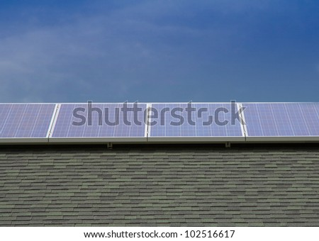 Photovoltaic Solar Panels Mounted on Roof with Blue Sky Background