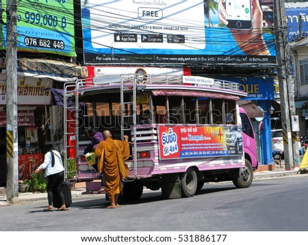 Phuket, Thailand - December 3, 2016: Colorful thai minibus in Phuket town on stop. People come out the bus. Monk in traditional orange clothes waiting for landing.