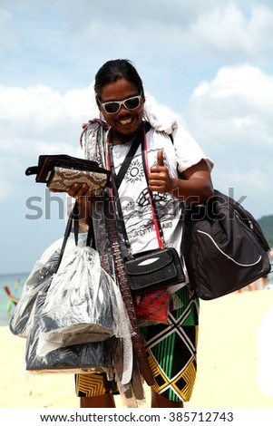PHUKET, THAILAND 10 december 2011 dark skin man sell bags and purses on the beach