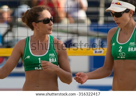 PHUKET, THAILAND-NOVEMBER 2: Maria Clara Salgado Rufino (L) of Brazil discusses game play with partner during match on Day 4 of Phuket Open on November 2, 2013 at Karon Beach in Phuket, Thailand