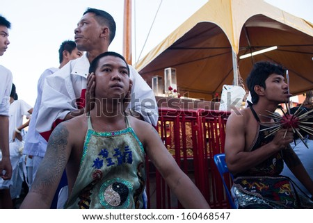 PHUKET, THAILAND - OCTOBER 10: An unidentified devotee (L) of Chinese shrine gets ready for piercing on his lips to take part in the 2013 Vegetarian Festival on October 10, 2013 in Phuket, Thailand