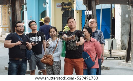 PHUKET, THAILAND SEPTEMBER 27: Tourists selfie at the walking street among old building Chino Portuguese style on street of Phuket town, Thailand on September 27, 2016.