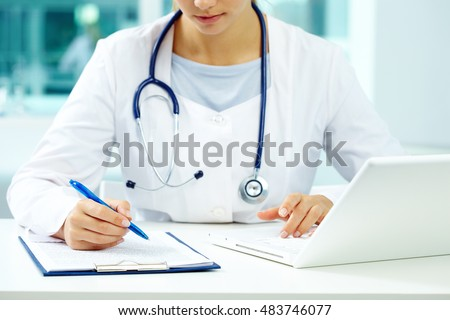Physician making notes in doctor office
